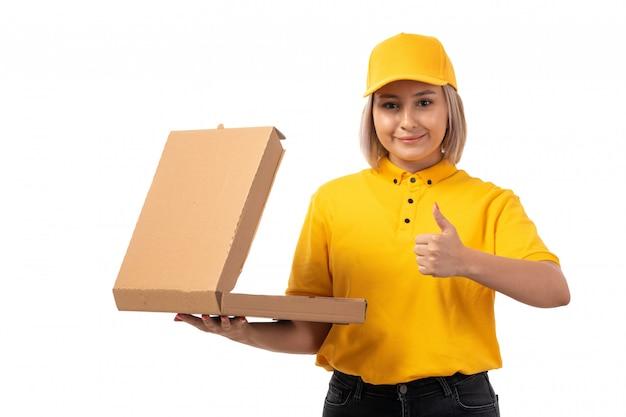 Widok z przodu żeński kurier w żółtej koszuli, żółtej czapce, czarne dżinsy, trzymając pudełko pizzy i uśmiechając się na białym tle