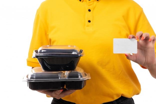 Widok z przodu żeński kurier w żółtej koszuli, żółtej czapce, czarnych dżinsach, trzymając miski z jedzeniem i białą kartką na białym tle