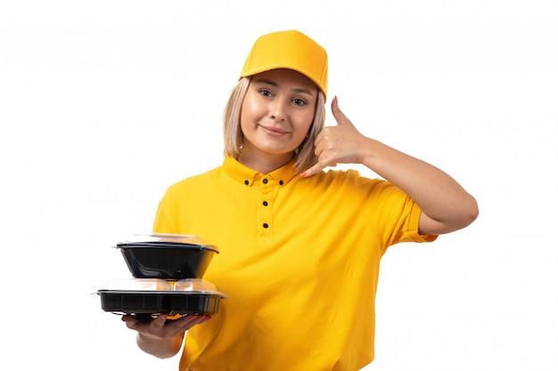 Widok z przodu żeński kurier w żółtej koszuli, żółtej czapce i czarnych dżinsach trzyma miski z jedzeniem i pokazuje znak wywołania telefonicznego uśmiechnięty na białym tle