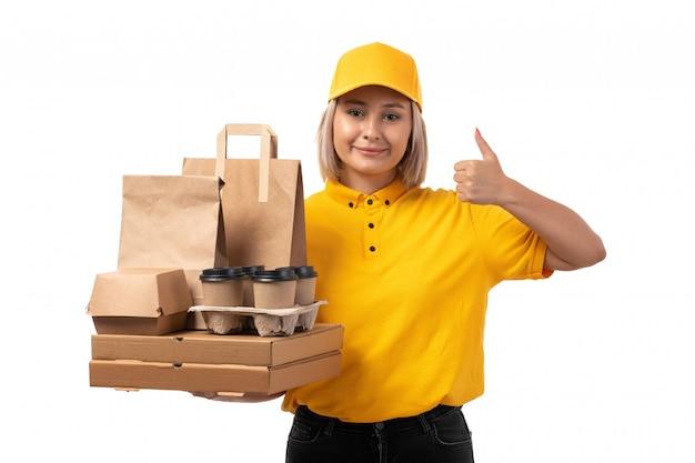 Widok z przodu żeński kurier w żółtej koszuli, żółtej czapce i czarnych dżinsach, trzymając pakiet z jedzeniem i filiżankami kawy na białym tle