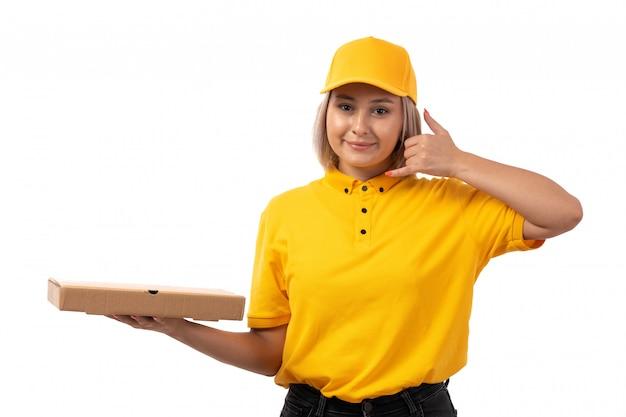 Widok z przodu żeński kurier w żółtej koszuli żółtej czapce i czarnych dżinsach uśmiechnięty trzymając pudełko po pizzy na białym tle