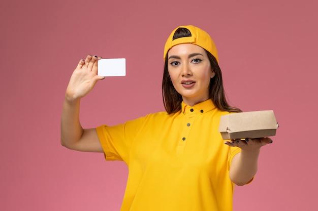 Widok z przodu żeński kurier w żółtym mundurze i pelerynie trzymający niewielką paczkę z dostawą żywności i kartę na jasnoróżowej ścianie usługi mundurowej firmy kurierskiej