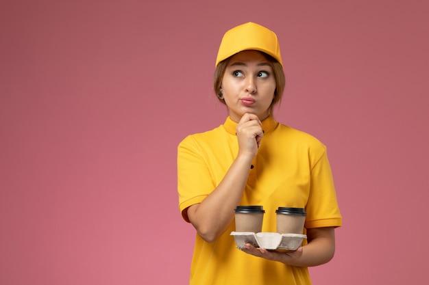 Widok z przodu żeński kurier w żółtym mundurze żółtej pelerynie trzyma kawę z myśleniem wyrazem na różowym tle praca jednolita dostawa