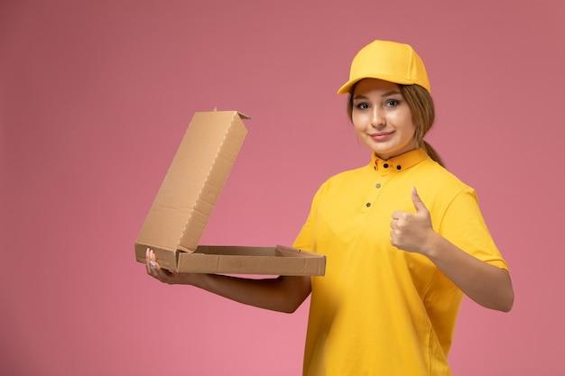 Widok z przodu żeński kurier w żółtym mundurze żółtej pelerynie trzyma pakiet dostawy żywności na różowym tle jednolita praca dostawy