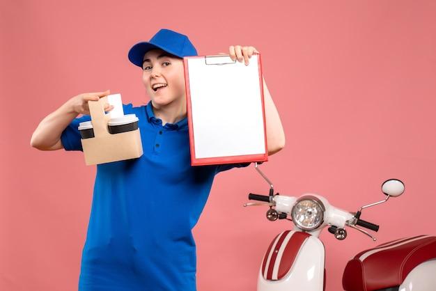 Widok z przodu żeński kurier z kawą i karteczką na różowym dostawie pracy jednolity pracownik usługowy pracownik pizza kobieta rower