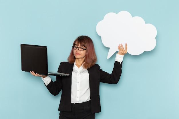Widok z przodu żeński pracownik biurowy posiadający duży biały znak i laptop na niebieskiej powierzchni