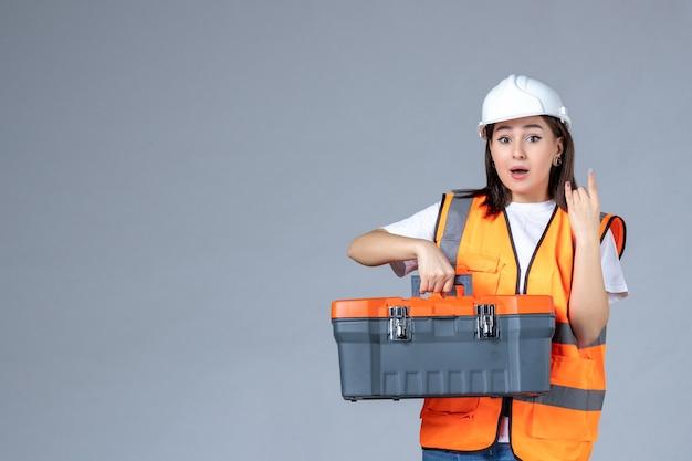 Widok z przodu żeńskiej konstruktorki z ciężką walizką narzędziową na szarej ścianie