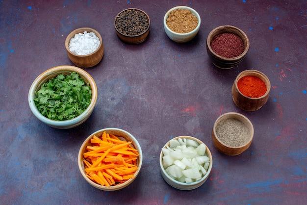 Widok z przodu zieleniny i przyprawy z pokrojoną cebulą na ciemnym biurku sałatka jedzenie posiłek przekąska warzywna