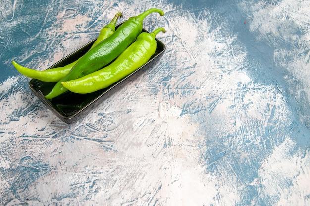 Widok z przodu zielona ostra papryka na czarnym talerzu na niebiesko-białym