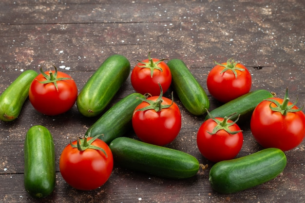 Widok z przodu zielone ogórki świeże i dojrzałe z czerwonymi pomidorami na brązowym, warzywnym pokarmie z drzewa roślinnego