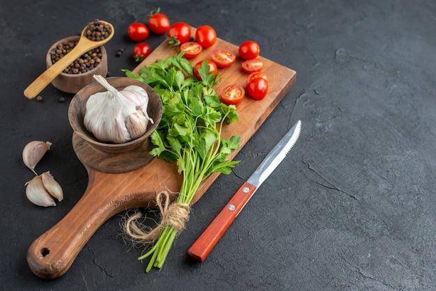 Widok z przodu zielonego pakietu świeże całe krojone pomidory czosnek na drewnianej desce do krojenia pieprz nożowy na czarnej trudnej powierzchni