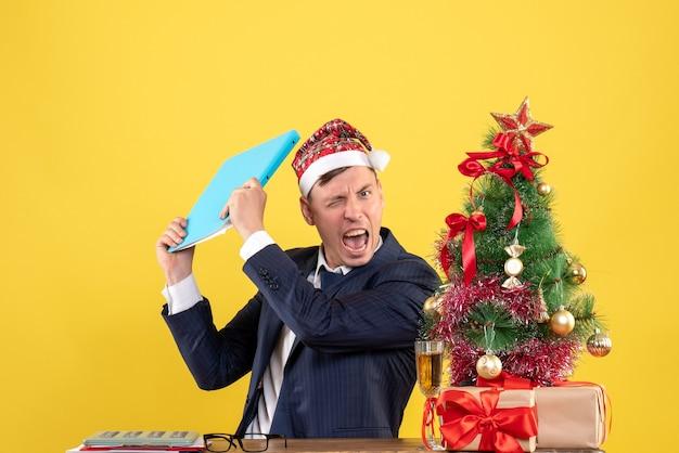 Widok z przodu zły biznesmen posiadający plik dokumentu siedzi przy stole w pobliżu drzewa boże narodzenie i przedstawia na żółtej ścianie