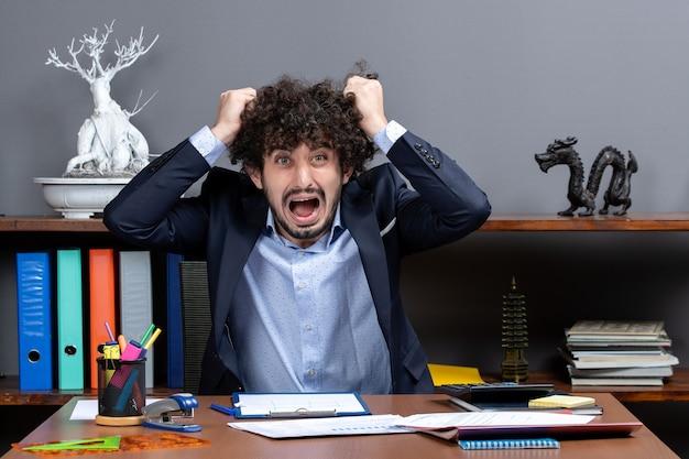 Widok z przodu zły biznesmen siedzi przy biurku i ciągnie za włosy