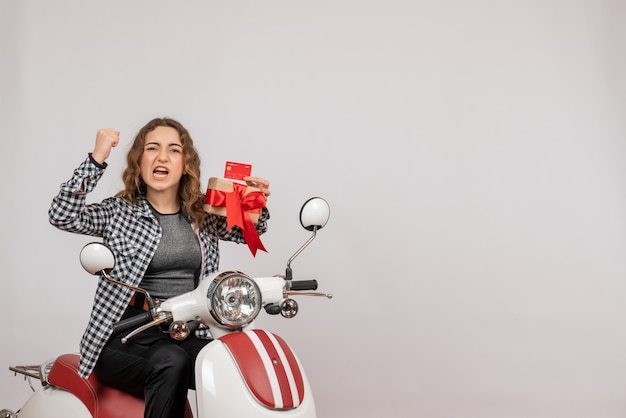 Widok z przodu zły młoda kobieta na motorowerze trzymając prezent na szarej ścianie