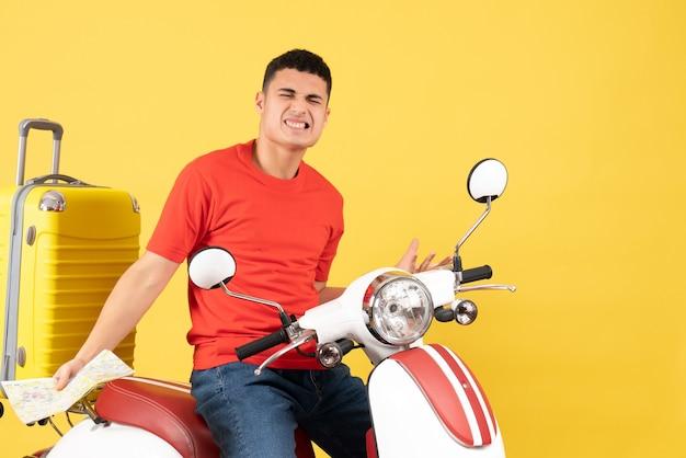 Widok z przodu zły młody człowiek na mapie gospodarstwa motoroweru