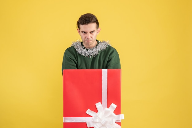 Widok z przodu zły młody człowiek stojący za dużym pudełkiem na prezent na żółto