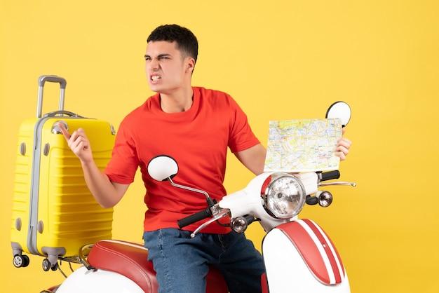 Widok z przodu zły młody człowiek w ubranie na mapie podróży motoroweru