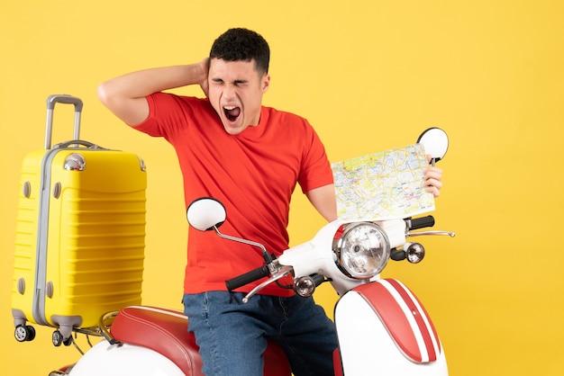 Widok z przodu zły młody człowiek w ubranie na motorowerze trzymając mapę podróży krzycząc
