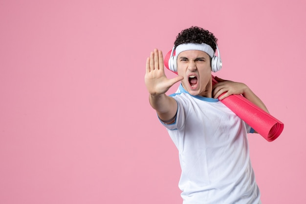 Widok z przodu zły młody mężczyzna w odzieży sportowej z matą do jogi