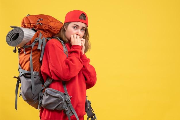 Widok z przodu zmartwiona podróżniczka kobieta w czerwonym plecaku na żółtej ścianie