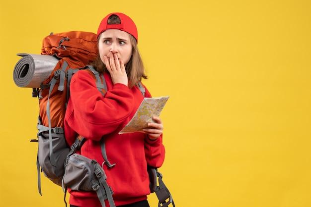 Widok z przodu zmartwiona turystka z czerwonym plecakiem trzymając mapę