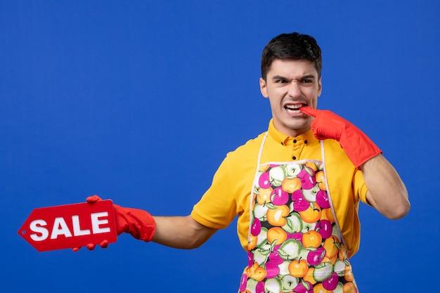 Widok z przodu zmartwionej męskiej gospodyni w żółtej koszulce trzymającej znak sprzedaży gryzący palec na niebieskiej ścianie