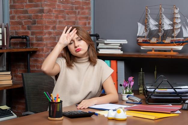 Widok z przodu zmęczonej kobiety biznesu siedzącej przy biurku w biurze
