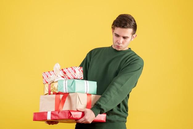 Widok z przodu zmęczony mężczyzna z zielonym swetrem, trzymając prezenty na żółto