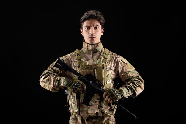 Widok z przodu żołnierza wojskowego w mundurze z karabinem na czarnej ścianie