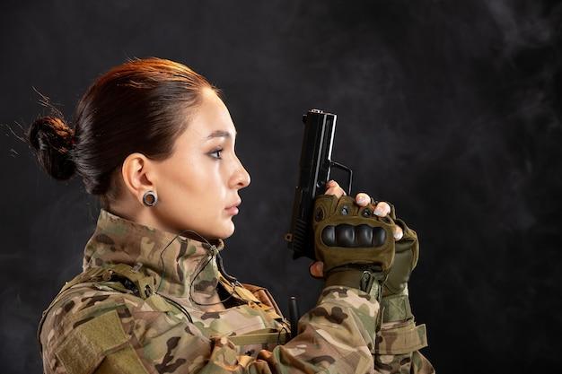 Widok z przodu żołnierza z pistoletem w mundurze na czarnej ścianie