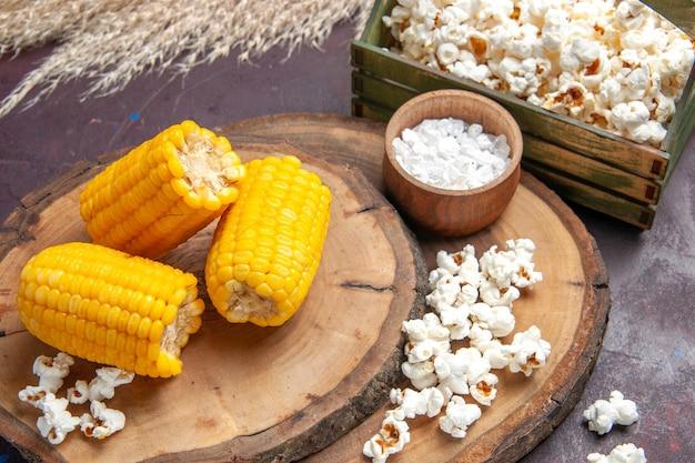 Widok z przodu żółte odciski pokrojone z popcornem na ciemnej powierzchni kukurydziana przekąska rośliny olej z drzewa