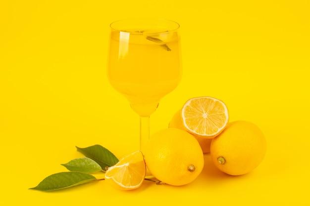 Widok z przodu żółte świeże cytryny świeże dojrzałe w całości i pokrojone w plasterki cytrynowy napój wewnątrz szklanych owoców odizolowanych na żółtym tle kolor owoców cytrusowych