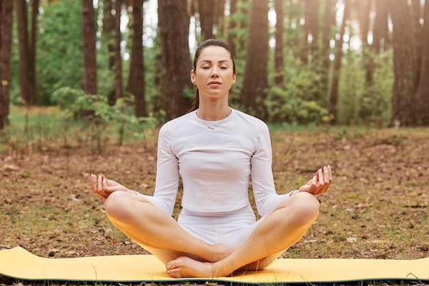 Widok z przodu zrelaksowanej sportowej dziewczyny z fryzurą w kucyk, siedzącej w pozycji lotosu na macie, z zamkniętymi oczami, skrzyżowanymi nogami