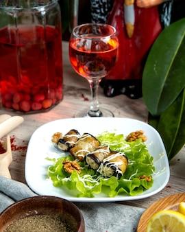 Widok z przodu zrolowany bakłażan z nadzieniem na liściu sałaty z orzechami włoskimi i szklanką campot