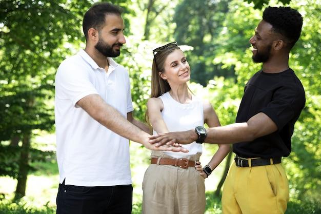 Widok z przodu zróżnicowana grupa przyjaciół, trzymając się za ręce