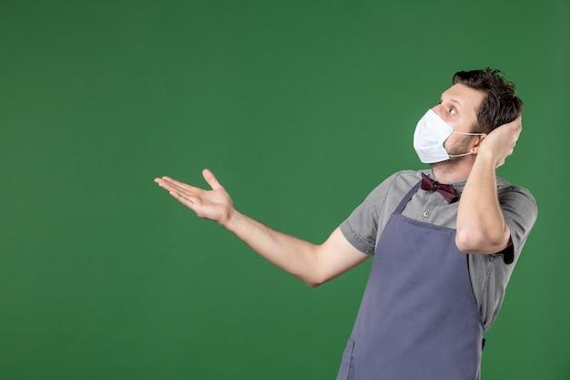 Widok z przodu zszokowanego kelnera faceta w mundurze z maską medyczną i wskazującym na prawą stronę na zielonym tle
