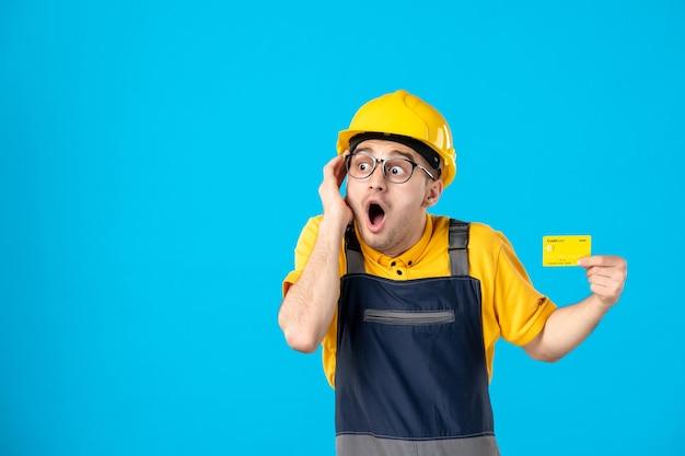 Widok z przodu zszokowanego konstruktora w mundurze i kasku z kartą kredytową na niebiesko