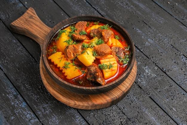 Widok z przodu zupa z sosem mięsnym z zieleniną i ziemniakami na ciemnym biurku zupa posiłek sos mięsny