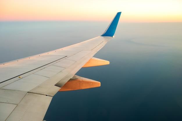 Widok z samolotu na białym skrzydle samolotu lecącego nad krajobrazem oceanu w słoneczny poranek.