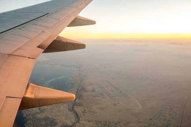 Widok z samolotu na białym skrzydle samolotu lecącego nad pustynnym krajobrazem w słoneczny poranek.