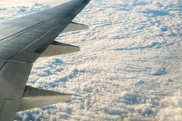 Widok z samolotu na białym skrzydle samolotu lecącego nad zachmurzonym krajobrazem w słoneczny poranek.
