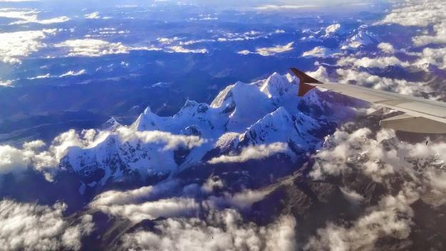 Widok z samolotu na skaliste góry pokryte śniegiem w słońcu w ciągu dnia