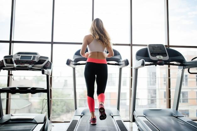 Widok z sportsmenka treningu na bieżni na siłowni z tyłu. kobieta fitness.