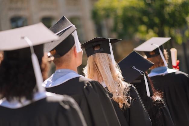 Widok z tyłu absolwentów w czapkach magisterskich odchodzących po uzyskaniu tytułu magistra