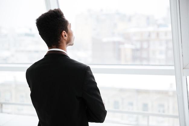 Widok z tyłu afrykańskiego biznesmena w czarnym garniturze patrzącego na okno w biurze