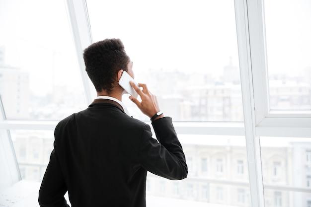 Widok z tyłu afrykańskiego biznesmena w czarnym garniturze rozmawiającego przez telefon i stojącego w pobliżu okna w biurze