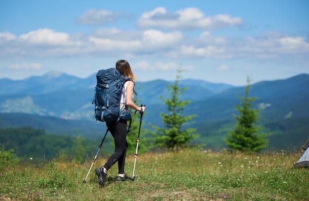 Widok z tyłu aktywnych kobiet podróżujących z plecakiem i kije trekkingowe