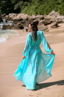 Widok z tyłu: atrakcyjna brunetka o szczupłym ciele i długich nogach pozuje w niebieskim bikini i niebieskiej pelerynie na plaży