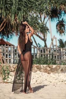 Widok z tyłu: atrakcyjna brunetka w czarnym ciele i półprzezroczystej plaży zakrywa pozowanie na piaszczystej plaży o zachodzie słońca. moda plenerowa strzał w lecie.