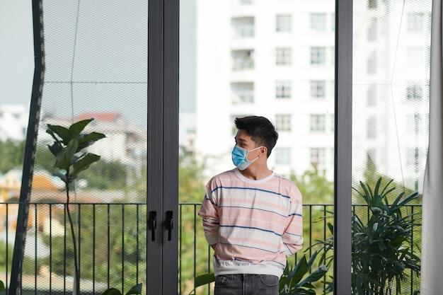Widok z tyłu azjatyckiego młodego mężczyzny noszącego maskę na twarz, pozostań w izolacji w domu, aby poddać się kwarantannie z powodu epidemii covid19 - wygląda przez okno
